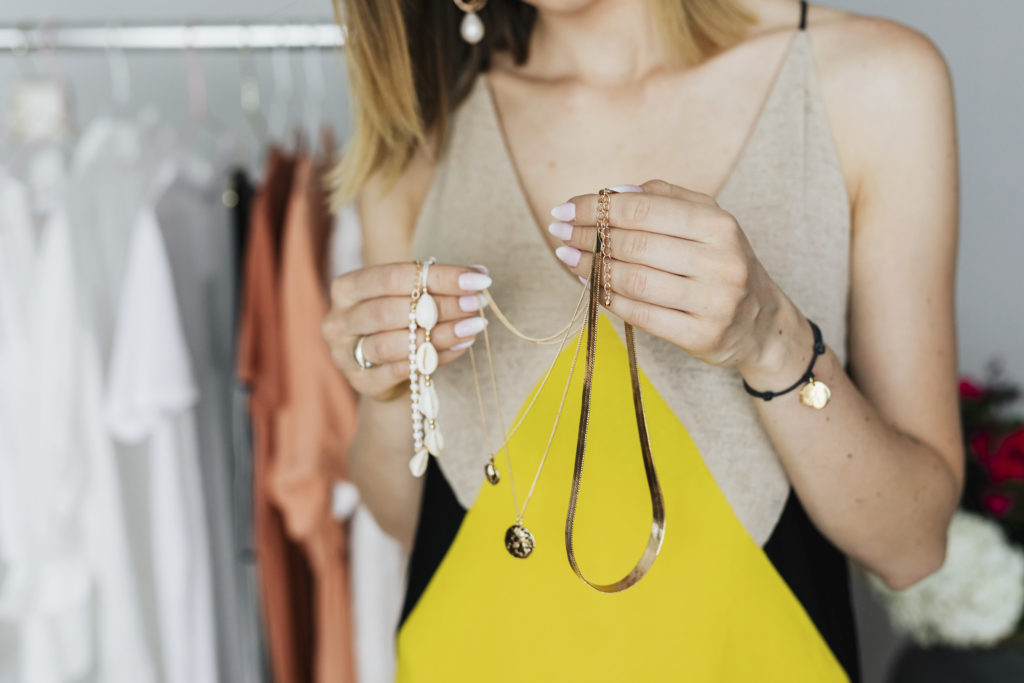 Woman holding necklaces in her hand while trying to choose the right necklace for her neckline
